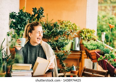 Young beautiful woman relaxing on cozy balcony, reading a book, wearing warm knitted pullover, holding cup of tea or coffee
