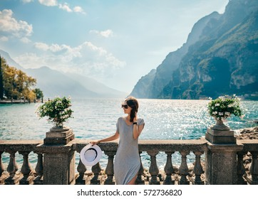 Young beautiful woman relaxing on picturesque Garda Lake. Vacation concept
