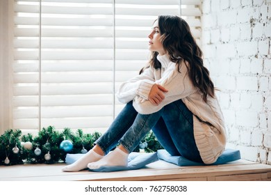 Young beautiful woman relaxing on window sill in christmas decorated home. Holiday concept