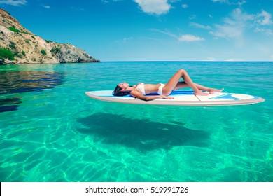Joven mujer hermosa relajándose en el mar en una tabla SUP. La chica se bañará en la playa de la isla de vacaciones.