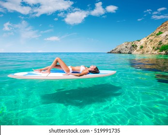 Young beautiful woman relaxing in the sea on a SUP board. The girl sunbathes on the beach of the island on vacation.