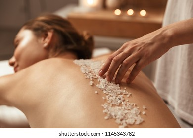 Young beautiful woman relaxing in the spa and having salt scrub massage at back