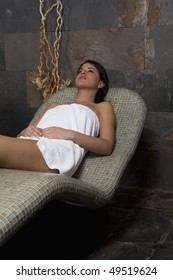 Young beautiful woman relaxing in stone bench in the spa.