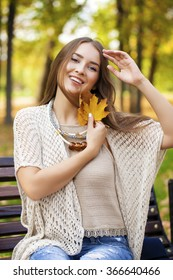 Young beautiful woman resting on a bench in the autumn park