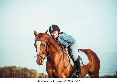 young beautiful woman rides a horse wearing a helmet. Horseback Riding.