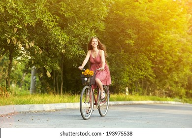 young beautiful woman riding a bicycle in a park. Active people. Outdoors