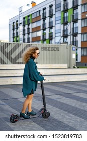 Young beautiful woman riding an electric scooter to work, modern girl, new generation, electric transport, ecology, ecological transport, sunset