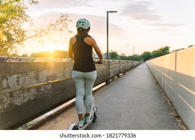 Young beautiful woman riding an electric scooter in a city park- concept of sustainable personal mobility