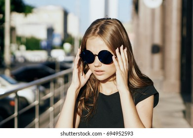 Young beautiful woman in round sunglasses in summer on the street.