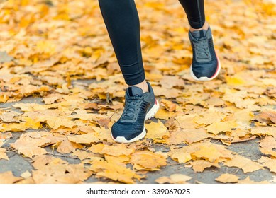 Young beautiful woman running in autumn park and listening to music with headphones. Legs close-up
