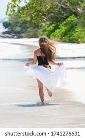 Young beautiful woman runs on a tropical beach