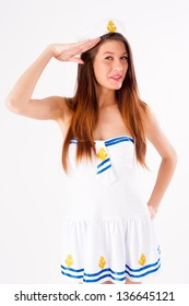 Young beautiful woman in sailor costume salute at white background