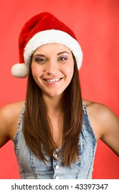 Young beautiful woman in Santa`s hat smiling in camera. Red background