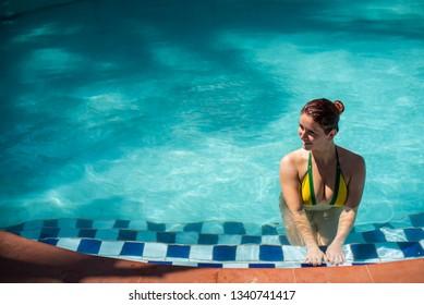 Young beautiful woman in seductive bikini at the pool. Brazilian flag. Redhead woman in swimsuit