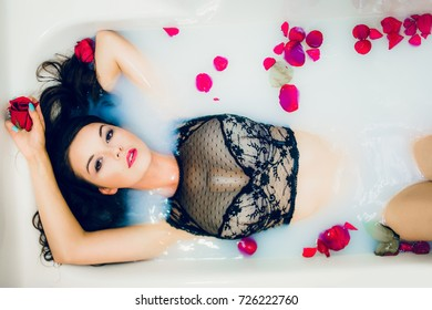 young beautiful woman in sexy lingerie with flowers relaxing in bathroom