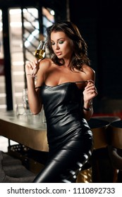 Young beautiful woman in sexy short black leather dress having good time in bar and drinking glass of wine or other drink. Stylish woman standing near bar counter