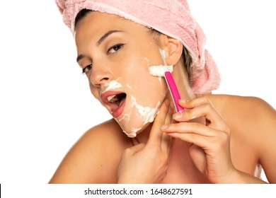 Young beautiful woman shaves her face on white background