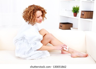 Young beautiful woman shaving her legs with electric epilator at home