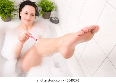 Young and beautiful woman is shaving her leg  in the bathtub