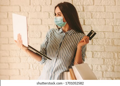 Young beautiful woman shopper in protective face mask hold laptop, credit card and shopping bags in hand. Happy girl in medical face mask shopping at online store. Coronavirus COVID-19, sale, discount