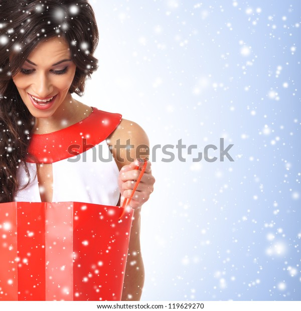 Young beautiful woman with the shopping bag over the Christmas background