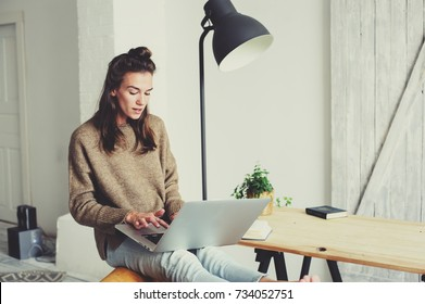 young beautiful woman shopping at home online with laptop and cup of coffee in the morning. Home office in modern scandinavian interior