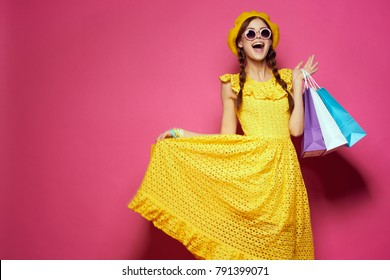 young beautiful woman with shopping on a pink background