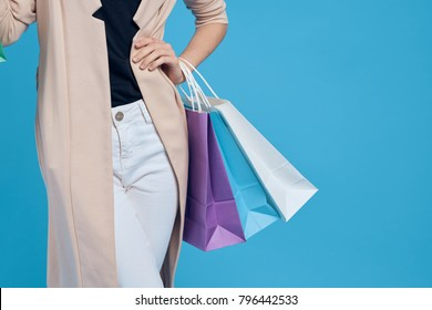 young beautiful woman with shopping on blue background