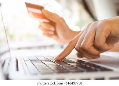 Young beautiful woman shopping online using laptop and credit card at home