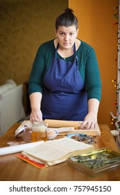 Young beautiful woman with short hair, standing in the kitchen behind a kitchen table, looking down at her hands. She is rolling a dough with a roller on a wooden board. Christmas baking concept