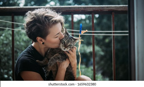 Young beautiful woman with short haircut holding and hugging a cute cat
