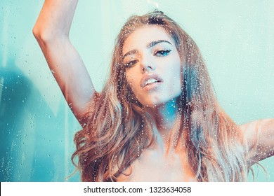 Young beautiful woman in shower. Behind wet glass window with water drops. Focus on droplets. Girl bathing, washing hair and taking fresh bath.