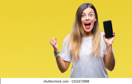 Young beautiful woman showing blank screen of smartphone over isolated background screaming proud and celebrating victory and success very excited, cheering emotion