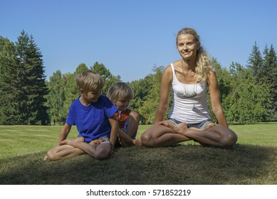 Young beautiful woman shows children the lotus position on the hands in park