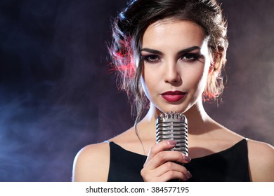Young beautiful woman singing in colourful smoke, close up