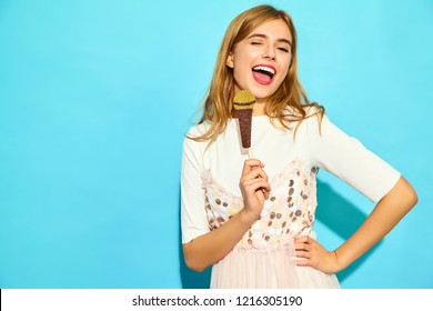 Young beautiful woman singing with props fake microphone. Trendy girl in casual summer clothes. Positive female emotion facial expression body language. Funny model isolated on blue background