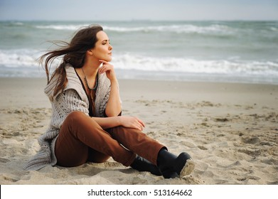 Young beautiful woman sit alone on a beach sand and look at the water, enjoy fresh air and weekends