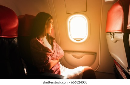 Young beautiful woman sit by window of airplane during flight