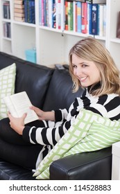 Young, beautiful woman sits on the couch and reads a book at home. A bookshelf is at the background.