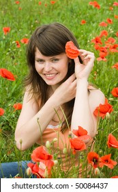 The young beautiful woman sits on a glade among red poppies.