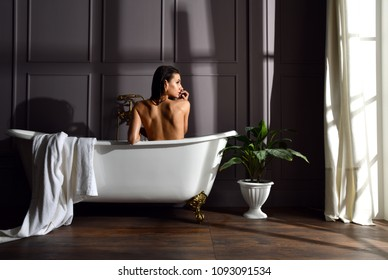 Young beautiful woman sitting in bathroom near expensive bathtub bath looking at the corner on dark background