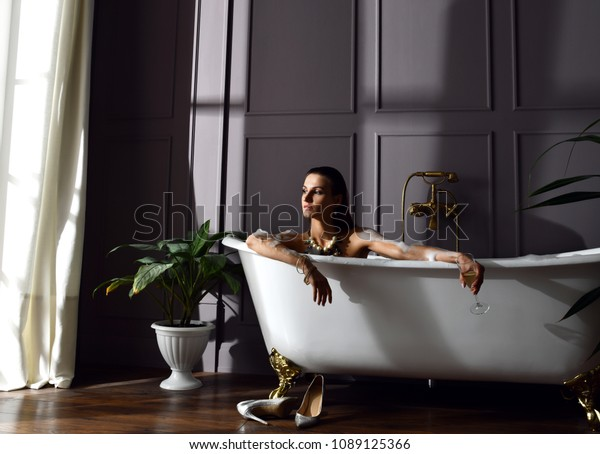 Side Profile Of A Young Woman Sitting In A Bathtub Stock