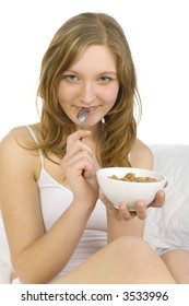 Young, beautiful woman sitting in bed and eating breakfast. Smiling and looking at camera. White background