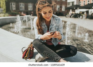 Young beautiful woman sitting in the city center checking her phone.