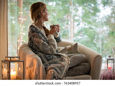 Young beautiful woman sitting home in the chair by the window with cup of hot coffee wearing knitted warm sweater. Cozy room decorated with lanterns and candles.