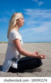 Young beautiful woman sitting in Lotus position on the beach meditating or performing yoga photographed from the side