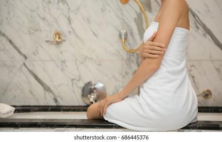 Young beautiful woman sitting in luxury bathroom