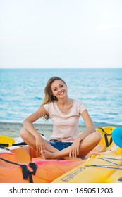 Young beautiful woman is sitting near the sea