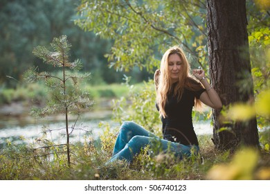 Young beautiful woman sitting near forest river and stretching, Russia, Siberia