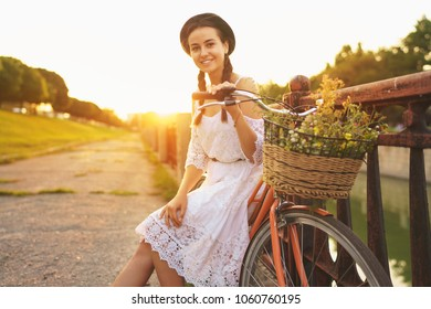 Young beautiful woman sitting on her bicycle with flowers at sunset. Summer and lifestyle